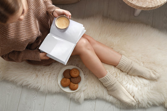 Young woman with cup of coffee reading book on rug at home, top view. Winter atmosphere