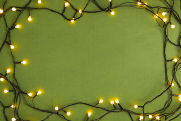 Fotobehang - Frame made with Christmas lights on green background, top view. Space for text