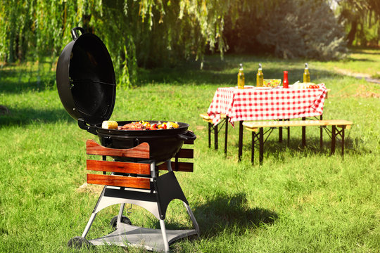Modern barbecue grill with tasty food in park