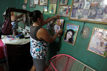 A relative arranges framed pictures of late Honduran migrant Herrera and her toddler at her mother's home in El Limon