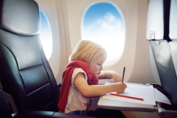Charming kid traveling by an airplane. Joyful little boy sitting by aircraft window during the flight. Child drawing picture.