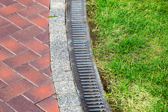 curve iron gutter with grate to the drainage system on the side of the walkway with green lawn on summer day in well maintained park.
