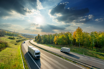 Fotobehang - Trucks driving on the asphalt highway between deciduous forest in autumn colors under the radiant sun and dramatic clouds. View from above.