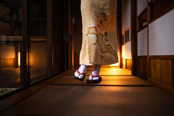 Traditional Japanese house ryokan closeup with tatami mat floor, shoji sliding paper doors, woman in kimono and geta shoes tabi socks walking in corridor hall room
