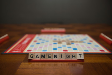 Letter tiles spelling out the words game night on stand in the foreground with out of focus game board in the background.