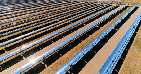 Solar panels in a solar farm in Spain. There is the reflection of the sun in the the panels which produce renewable energy, solar energy - close-up with a drone - environment and renewable energy conc