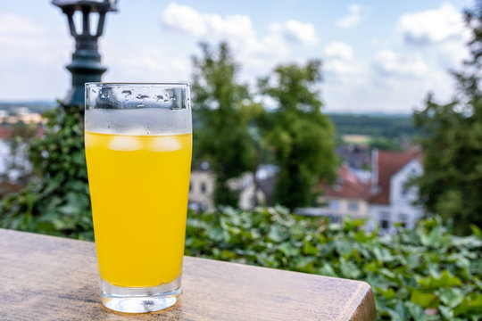 yellow softdrink sitting next to a view in bad bentheim, germany. bright sunny day in July.