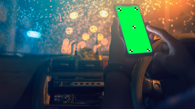 Driver uses the phone screen green background Bokeh on the street on a rainy day.Soft focus.