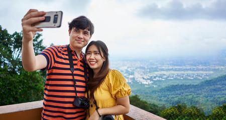 thai tourist couple taking selfie at  Wat Phrathat Doi Suthep temple in chiang mai thailand
