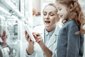 Pharmacist showing pictures of vitamins in the tablet to baby-girl