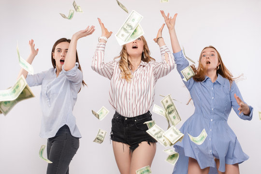 Three excited and shocked women with arms up trying to catch flying dollars or bucks in the air. Money flying in the air.