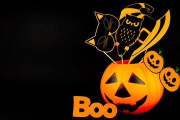 Cauldron smiling pumpkin with funny paper photo props, masks, photobuthoria: witch hat, cat, owl, eyes on black background. Party accessories for celebrating happy halloween. Orange inscription boo.