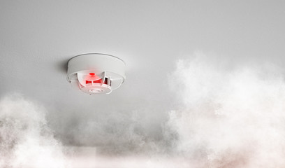 close-up of smoke alarm or smoke detector in home going off with thick smoke