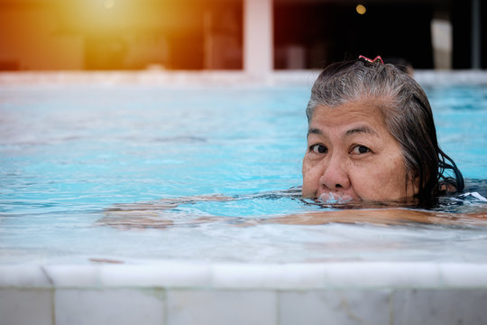 Asian women are swimming in the pool for relaxing on a holiday trip. Activities for improving the quality of life of an elderly women.