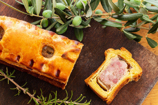 Top view of a pate en croute or pâté en croûte, with rosemary twig and green olives on branch with leaves over a dark wooden cutting board background. French traditional appetiser.