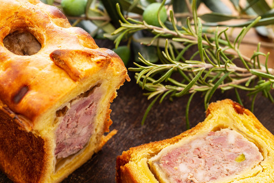 Pate en croute or pâté en croûte or meat pie, with rosemary twig and green olives on branch with leaves over a dark wooden cutting board and a used oak wood background. French traditional appetiser.