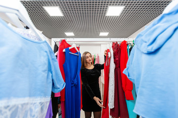 Happy young woman choosing clothes in mall or clothing store. Sale, fashion, consumerism concept