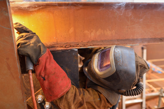 Macro pic of maintenance welder wearing red safety glove welding helmet with power air purifying respirator while performing welding a difficult task condition to protect from the toxic fume