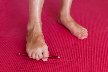 Girl doing exercises with a pencil for toes. Close-up Wall mural