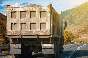 Rear view on a large dump truck rides on a highway in the mountains while transporting goods over long distances. Fast delivery by ground transportation.