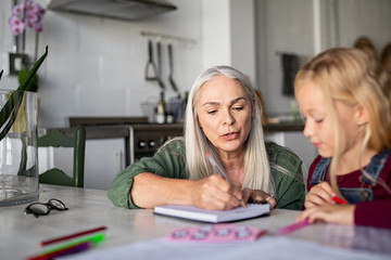 Grandmother teaching to granddaughter at home