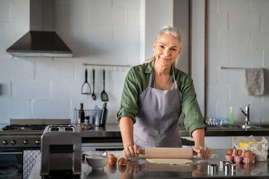 Happy senior woman rolling dough