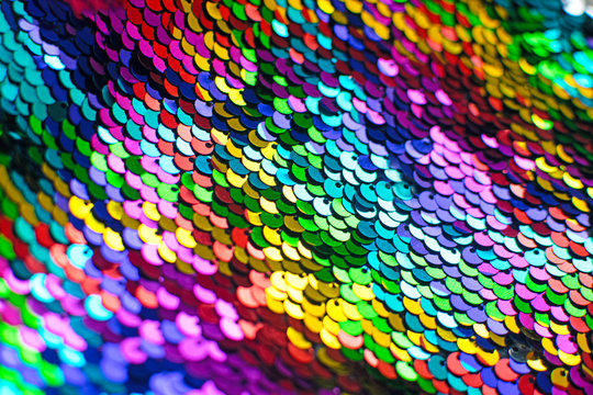 Texture of rainbow shiny sequins. Fashionable bright fabric with sequins. Selective focus.