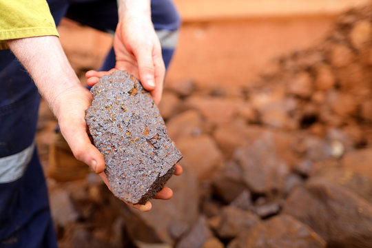 Close up picture of scientist geologist hands inspecting exploration on iron ore rock on open field mine site, Perth, Australia
