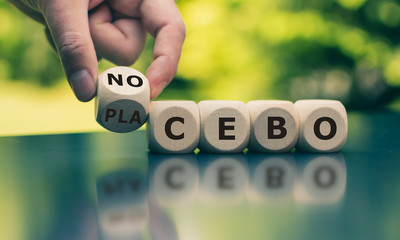 """Nocebo or placebo? Hand turns a cube and changes the word """"placebo"""" to """"nocebo"""", or vice versa."""