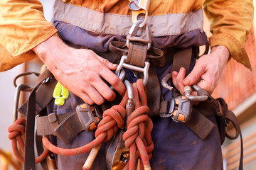 Closeup picture of male rope access worker hand wearing full safety harness clipping carabiner on a chair into harness loop prior to abseiling working at height construction site, Sydney, Australia