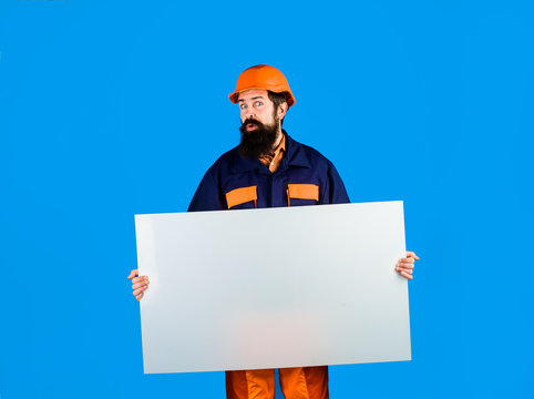 Builder, repairman in protective helmet holds empty board with space for text. Man builder holds advertising banner, billboard, sign board. Construction worker, engineer, architect with blank board.