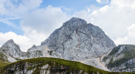 Panorama of western wall of Mount Mangart with Hikers in the Julian Alps. Shoot from Mangart Saddle, Mangartsko sedlo. Border of Slovenia and Italy
