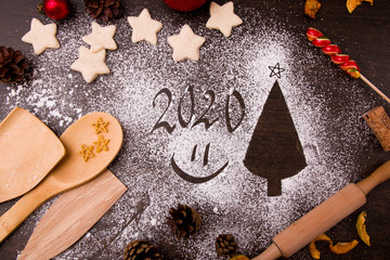 Christmas tree made of flour, Christmas decor,, the process of baking cookies in the shape of stars, kitchen utensils, dark brown wooden table background, Christmas background, copy space, top view