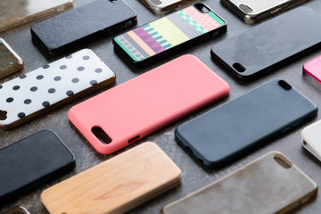 Pile of multicolored plastic back covers for mobile phone. Choice of smart phone protector accessories background. A lot of silicone phone backs or skins next to each other