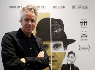 """Uruguayan auteur Federico Veiroj poses for a picture in front of the poster of """"The Moneychanger"""" film in Buenos Aires"""