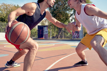 Image of sporty men playing basketball on playground on summer day.