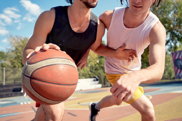 Picture of sportsmen playing basketball on playground on summer day.