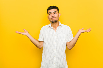 Young hispanic man confused and doubtful shrugging shoulders to hold a copy space. Wall mural