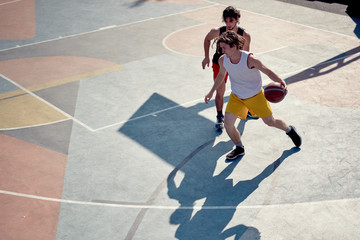 Top view of two young sporty men playing basketball on playground in morning .
