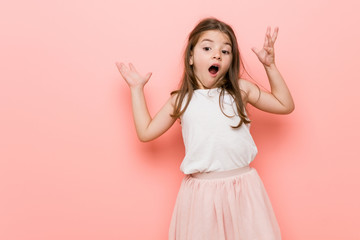 Little girl wearing a princess look receiving a pleasant surprise, excited and raising hands.