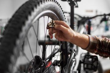 Cropped shot of serviceman working in bicycle repair shop, mechanic repairing bike using special tool