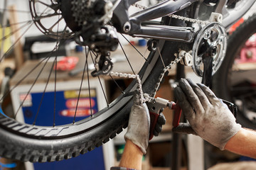 Cropped shot of professional mechanic working in bicycle repair shop, serviceman repairing bike chain using special tool, wearing protective workwear and gloves