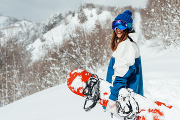 laughing happy girl with a snowboard and background of mountains and snowy trees.