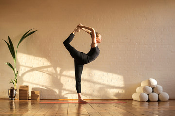 Wall Murals Yoga school Beautiful woman doing yoga at sunset time in a studio