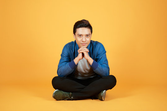 Good looking young Asian man sitting with legs crossed on the floor, isolated on orange background.