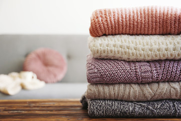 Bunch of knitted pastel color sweaters with different knitting patterns perfectly folded in stack on brown wooden table, white brick wall background. Fall winter season knitwear. Close up, copy space