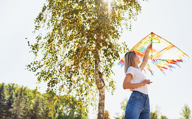 Outdoor image of happy young woman is launching a kite on a sunny day in the summer. Beautiful female playing and have fun outside with a kite in the park.