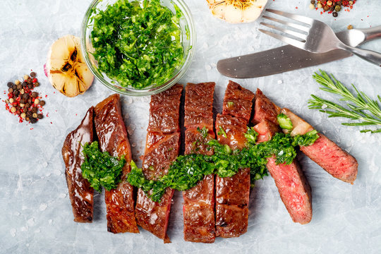 Sliced rib eye beef steak with chimichurri sauce and spices on white paper. Striploin cooked on the grill, top view