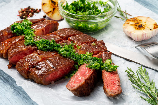 Sliced grilled rib eye beef steak with chimichurri sauce on white paper on wooden background. Concept of cooked steak