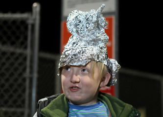 A boy wears a tinfoil hat at the gates of Area 51 as an influx of tourists responding to a call to 'storm' Area 51, a secretive U.S. military base believed by UFO enthusiasts to hold government secrets about extra-terrestrials, is expected in Rachel